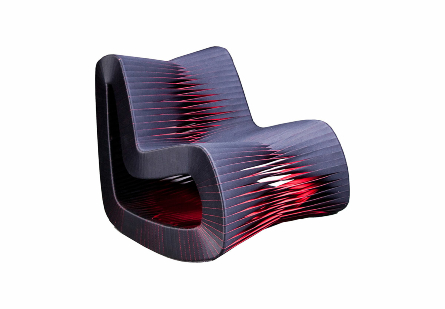 angled view of the Phillips Collection Seat Belt Black Red Rocking Chair which is made of straps woven to create a sculptural shape from interlocking bands