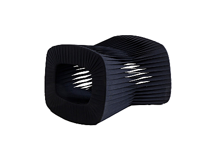 angled view of the Phillips Collection Seat Belt Black Ottoman which is made of straps woven to create a sculptural shape from interlocking bands