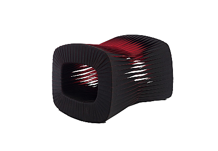 angled view of the Phillips Collection Seat Belt Black Red Ottoman which is made of straps woven to create a sculptural shape from interlocking bands