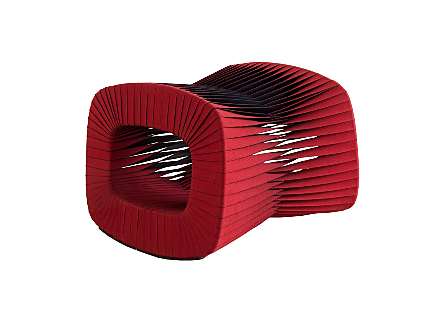 angled view of the Phillips Collection Seat Belt Red Ottoman which is made of straps woven to create a sculptural shape from interlocking bands