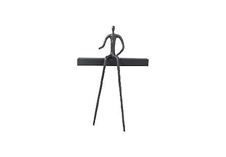 front view of the Short Moveable Pointing Man Shelf by Phillips Collection with a whimsical bronze figure that can move around its black wood shelf